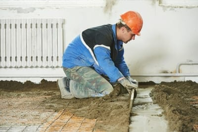 worker applying the first layer of concrete on a residential floor at melton concreters